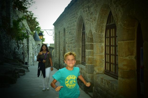 niño - niño corriendo - casas - calle - piedras